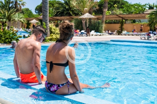 Couple d'ado assis au bord de la piscine